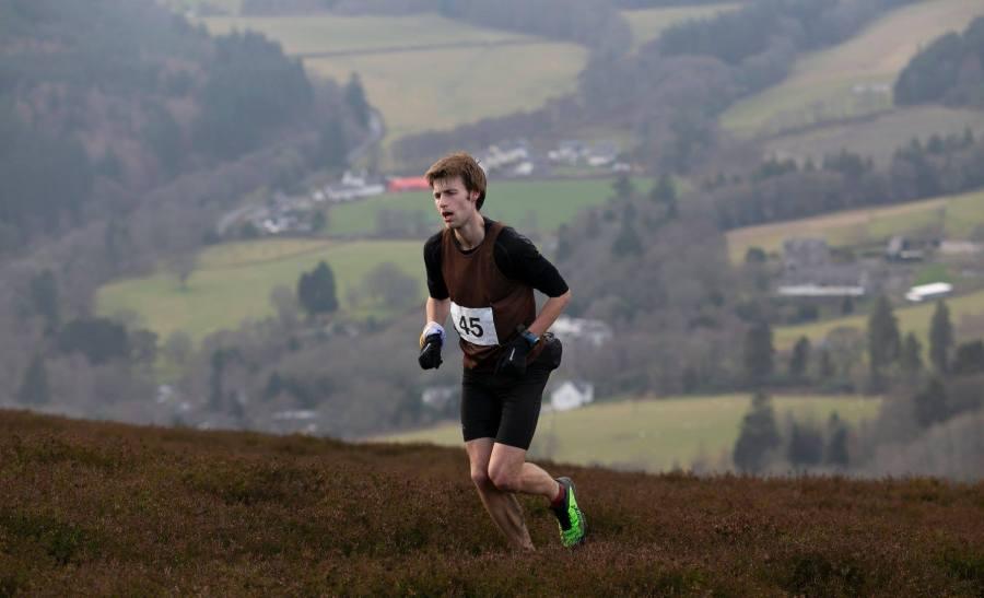 Hill runner number 45 in brown vest heading up heather hillside.